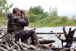 man with binoculars on the hunt