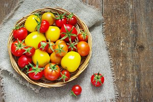 tomatoes in  wicker basket on a wooden table