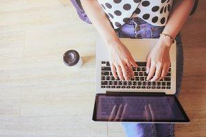laptop in girl's hands on floor