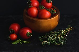 Ripe cherry tomatoes in wooden bowl