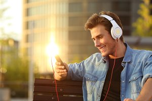 Happy man listening to music from a smart phone.jpg