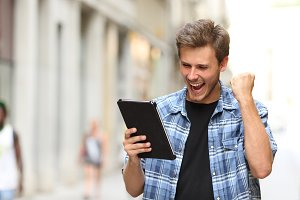 Euphoric winner man with a tablet.jpg