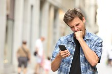 furious angry man watching mobile phone.jpg
