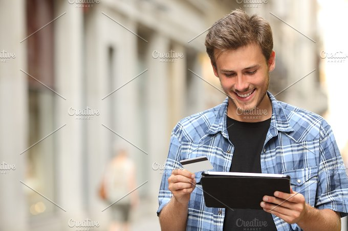 Man buying online with a credit card and a tablet.jpg - Technology