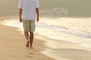 Man walking and leaving footprints on the sand of a beach.jpg