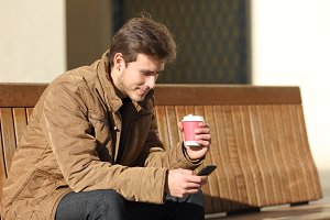 Man using a smart phone and holding a coffee cup.jpg