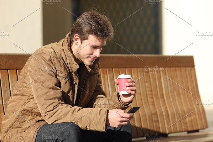 Man using a smart phone and holding a coffee cup.jpg - Technology