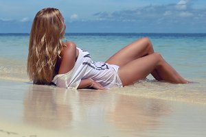 young blonde lying on the beach