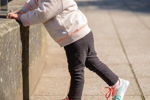 Girl with sneakers warming outdoors