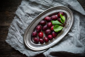 Red plums on silver tray
