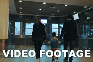 Family of three walking in airport