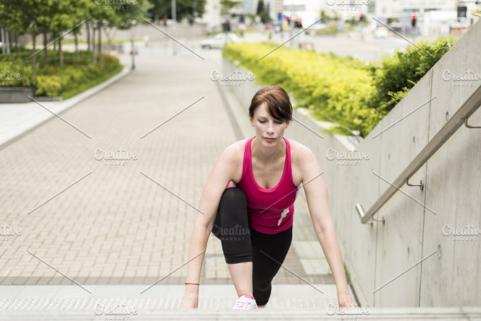 Cute Woman stretching her muscles on a steps.jpg - Sports