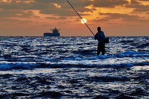 Man fishing in the sea surf at sunse