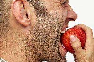 Man expressively bites red  apple