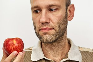 Man looking at the red apple