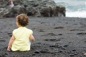 Baby view from behind, on the beach.