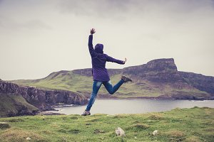 Woman jumping in the green meadows