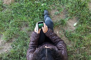 Woman under a tree using mobilephone