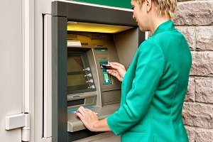 Business woman operates an ATM