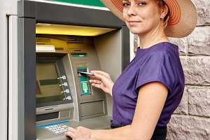 Pretty woman operates an ATM
