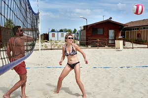 Man and girl play volleyball