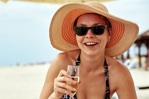 Beautiful girl in hat with champagne