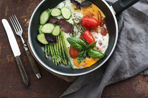 Pan of fried eggs and vegetables