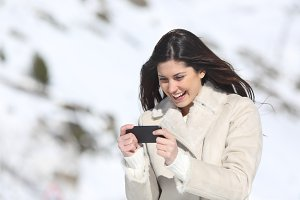Woman playing games in a smart phone on winter holidays.jpg