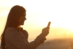 Woman silhouette using a smart phone at sunset.jpg