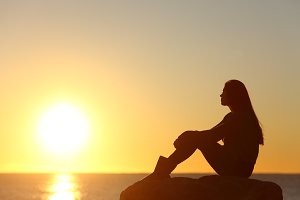 Woman silhouette watching sun in a sunset.jpg