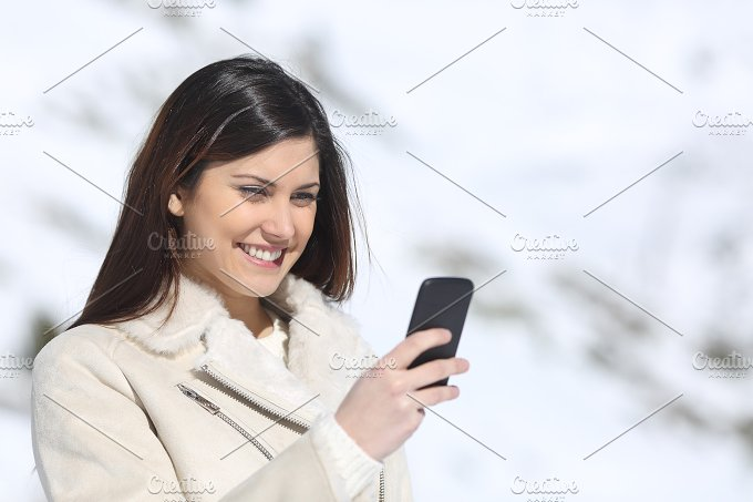 Woman using a smart phone on winter holidays.jpg - Technology