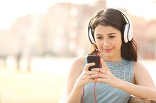 Girl searching songs and listening music with headphones.jpg