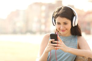 Girl listening music with headphones from a smartphone.jpg