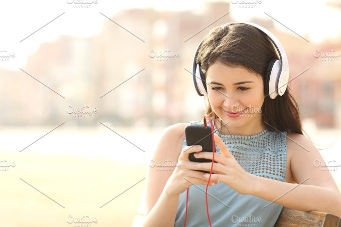 Girl listening music with headphones from a smartphone.jpg - Technology