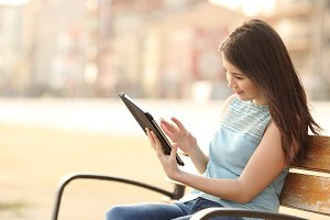 Girl reading a ebook or a tablet in a park.jpg