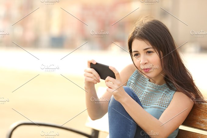 Funny teenager playing games on a smart phone.jpg - Technology