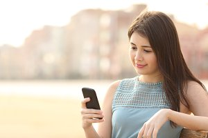 Pretty girl using a mobile phone in an urban park.jpg