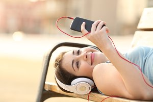Teen girl listening music from a phone lying in a bench.jpg