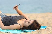 Teen girl lying and using a smart phone.jpg