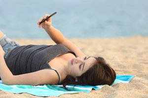 Teen girl lying and using a smart phone.jpg