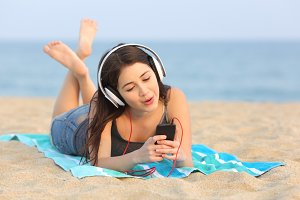 Teen girl listening music and singing on the beach.jpg