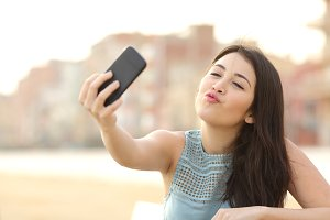 Teen girl photographing a selfie with a smart phone.jpg