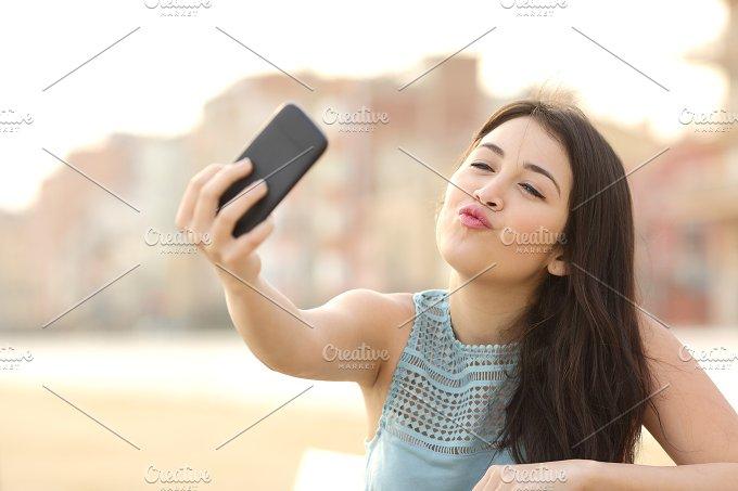 Teen girl photographing a selfie with a smart phone.jpg - Technology