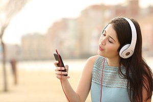 Teen girl singing and listening music from a smart phone.jpg