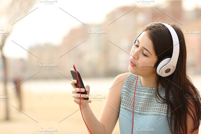 Teen girl singing and listening music from a smart phone.jpg - Technology