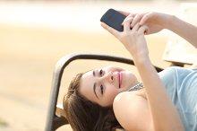 Teen girl using a smart phone lying in a bench.jpg