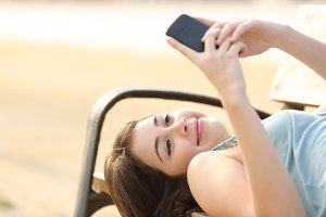 Teen girl using a smart phone lying in a bench.jpg