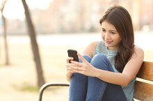 Teen girl using a smart phone sitting in a bench.jpg