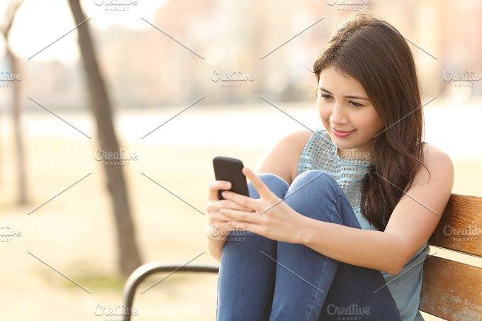 Teen girl using a smart phone sitting in a bench.jpg - Technology