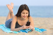 Teenager girl texting a smart phone lying on the beach.jpg